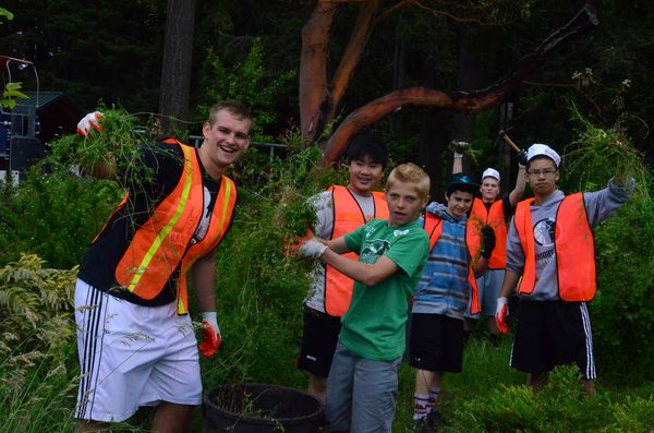 Group mentor Ryker Young and student Jacob Ganz are all smiles as they yank out weeds by the handful.
