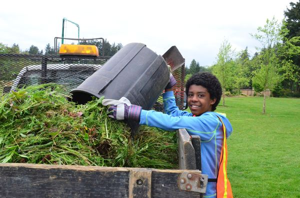 - Lewi Hugo of Shoreline dumps a trash can full of weeds into the waiting truck.