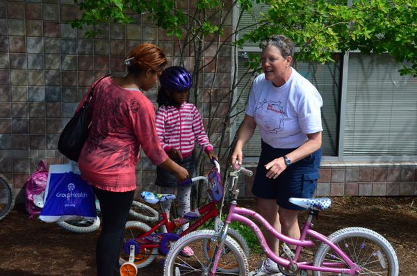 Madrona teacher and event coordinator Amy Rust assists at the bicycle exchange, where kids could trade in a bike they've outgrown for a larger model.