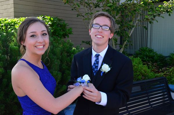Taylor Sharp places a corsage on Amy Rickel's wrist.