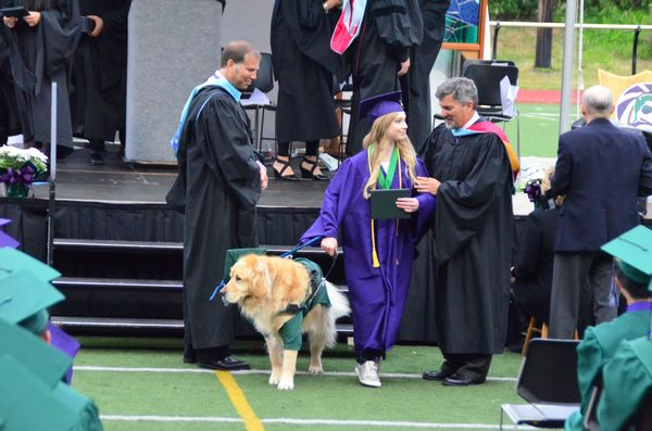 Maggie Mittelstaedt, with her service dog, leave the stage after she receives her diploma.