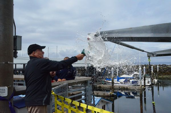 Mike Deller of the State Recreation and Conservation Funding Board (CFB) breaks a bottle of champagne on the lift, officially christening the new boat launch.