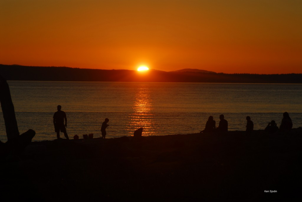 After another warm summer day, people gather on the Edmonds waterfront to watch the sunset Monday evening. (Photo by Ken Sjodin)