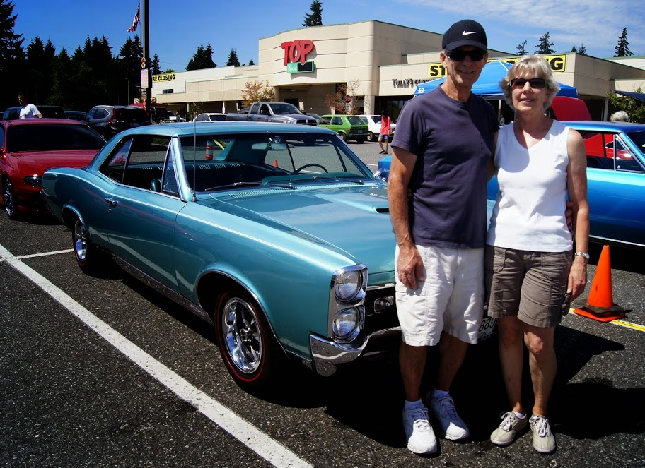 """Terry and Ruth Taylor, of Edmonds, with their pristine Pontiac GTO, which they bought brand new back in 1967. Terry bought it for the 360 horsepower, and Ruth bought it for the power brakes, power steering and automatic transmission. It has only 50,000 miles. """"Terry purchased it for just under $4,000, and when I took out my wallet and asked, """"How much would you take for it now?"""" he said 35, """" Carlos said. """"To which Ruth quickly said, 'No!' It's been such a part of their lives she doesn't want to sell it. Luckily, I didn't have $35,000 anyway."""