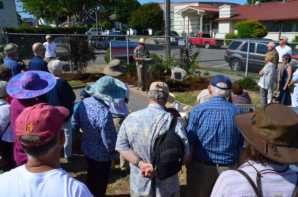 A crowd of almost 50 friends and family listen to Dick Van Hollebeke, member of the Edmonds Petanque club and longtime friend of Chris Guitton.
