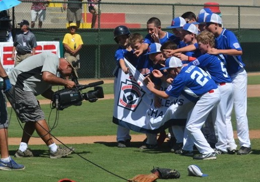 Pacific Little League players celebrate winning the Northwest Regional title in front of a cameraman from ESPN, which broadcast the game.