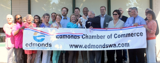 Lynnwood Mayor Nicola Smith, Snohomish County Executive John Lovick and Lynnwood City Council President Loren Simmond (center) along with the Edmonds Chamber of Commerce cut a ribbon in recognition of the remodeling of the Clothes for Kids store in Lynnwood. (Photos by David Pan)