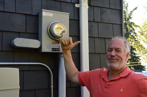 Dan Fine stands next to the state-of-the-art electric meter that measures electricity flowing both in and out of their home. When the Fine's photovoltaic system is producing more electricity than is needed to meet their home power demand, the surplus flows back into Snohomish PUD's system, earning them credit on their electric bill. At the time this photo was taken, power was flowing back to the PUD. Here Dan raises his thumb to show the direction of power flow.