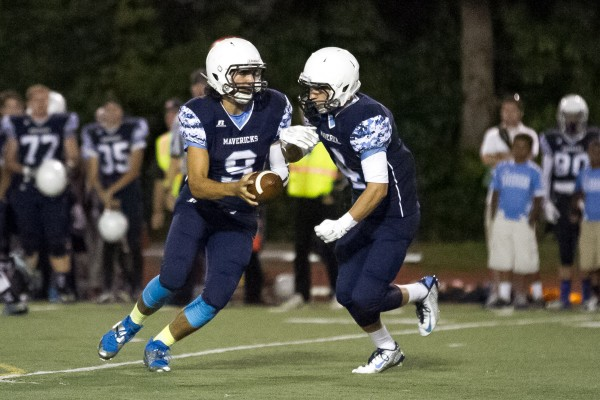 Meadowdale quarterback JP Routen hands off to Spillum.