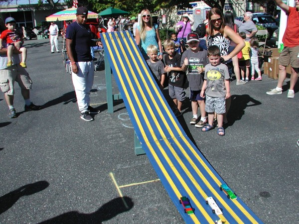 Children and their parents enjoy the pine box derby races in the Kids Corner. (Teresa Wippel photo)