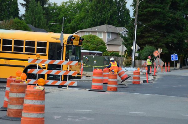 Crews remove the final barriers to allow the first vehicle, a school bus, onto the new roundabout roadbed.