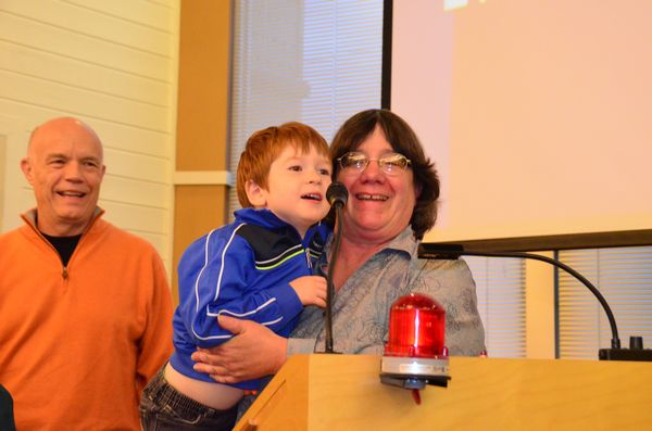 """Edmonds Museum Board member and Scarecrow Festival project manager Dave Buelow looks on as  Councilmember Lora Petso boosts her grandson, four-year-old Augustine """"Gus"""" Nishino, to the podium to address the Edmonds City Council."""