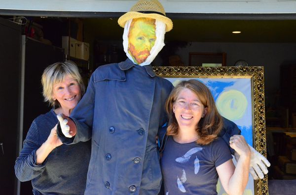 "Vincent van Go-Crow, flanked here by creators Mona Smiley-Fairbanks (R) and Robin Westbrook (L), is the first entry in this year's Edmonds Scarecrow Festival to hit the streets. Go-Crow is now displayed on ""the fence,"" an outdoor display area adjacent to the ArtWorks at Second in Dayton in downtown Edmonds."