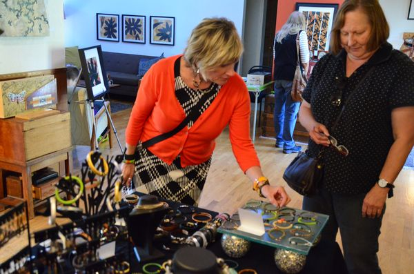 Robin Westbrook explains her custom jewelry to a studio tour participant.