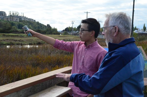 Retired Edmonds High School biology teacher John Cooke discusses how to improve salmon habitat at the Edmonds Marsh with Evan Zhao, Edmonds-Woodway senior and member of the Students Saving Salmon group.