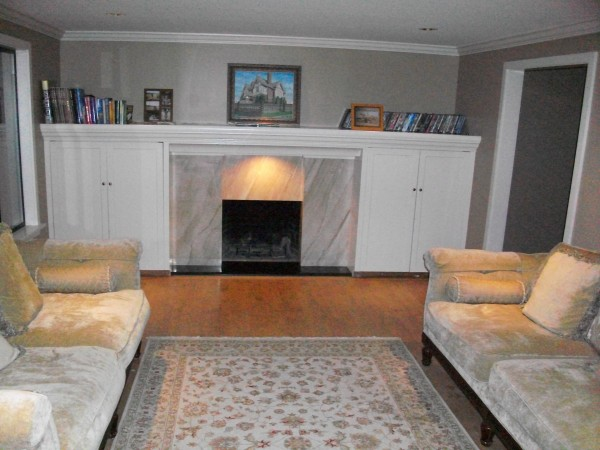 The living room.  Four-inch-wide maple floor boards.  Scorpio marble fireplace.  Galaxy black granite hearth.  Entertainment centers on both sides of the fireplace -- capped with a 24-foot long mantle. Light over fireplace.