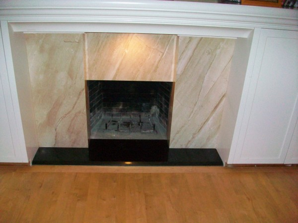 The living room fireplace.  Scorpio marble and galaxy black granite hearth.  Mitered columns with bevel on front of hearth.