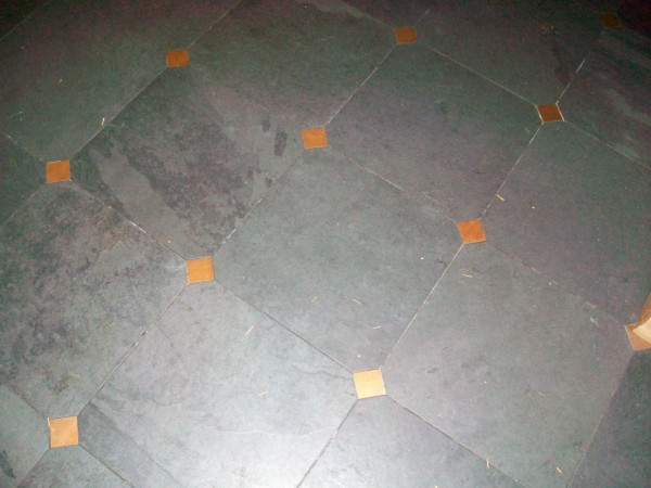 Kitchen floor close up.  16 inch by 16 inch Brazilian black slate floor with 2-inch-by-2- inch copper drops on corners.