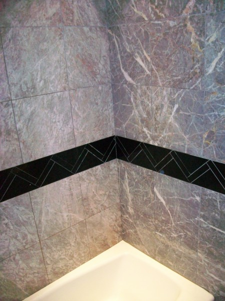 Upstairs bath.  Signature border.  Absolute black granite Fiore' de Pesco Carnico vein matched walls.  Crown molding touching the ceiling around the entire room.