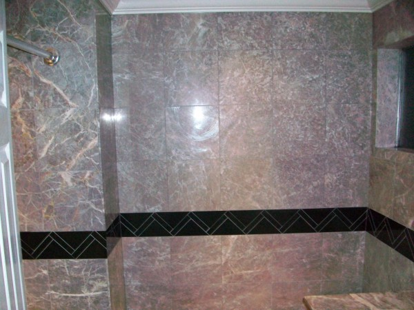 Tub enclosure.  Fiore' de Pesco Carnico vein matched marble tiles from tub to ceiling crown molding.  Absolute black granite signature border around the room.