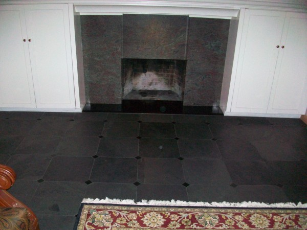 Family room fireplace and floor. Lila Jurais granite fireplace with miterd columns and bevel on the Galaxy black granite hearth. Brazilian black slate floor 16 inch by 16 inch with 2-inch-by-2-inch Galaxy black granite drops on corners.
