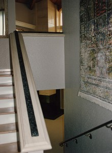 Staircase walls, railing and stone capping. Note on the right the antique bronze finish on solid brass railing going downstairs over slab staircase. Claire Limestone Slab wall cap with English Brown Granite hand grip leading upstairs.