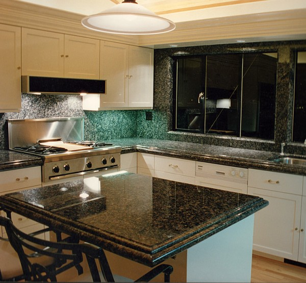 The kitchen at night: A view of the lighting used under the upper cabinet, over countertops, around the room and over the island, all on dimmers.