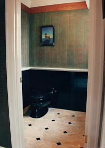 Master Bathroom toilet room.  Absolute Black Granite wainscoting with black toilet to match walls.  Breccia Oneciata Marble floor – vein matched with 2-inch-black granite dots on corners.  Embossed paper walls – faux finished resembling untarnished copper and ancient copper patina.  A Maxfield Parish print is on the wall.