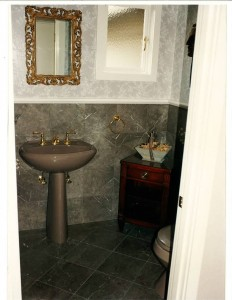 A close-up view of the powder room showcases the St. Thomas Lila Marble walls and floor – vein matched. Embossed wallpaper above wainscoting is faux finished with all embossed flowers hand-painted.