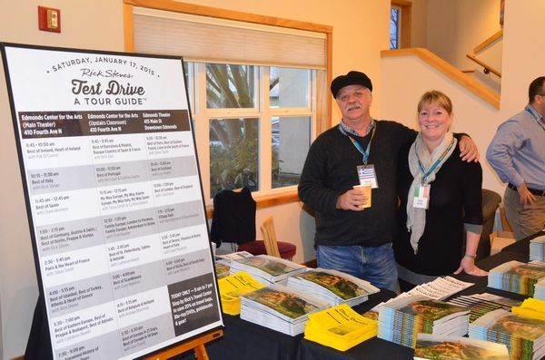 Dave Willet from Greece and Susie Millar from Ireland greet Rick Steves tour alums at the information desk in the Edmonds Convention Center lobby.
