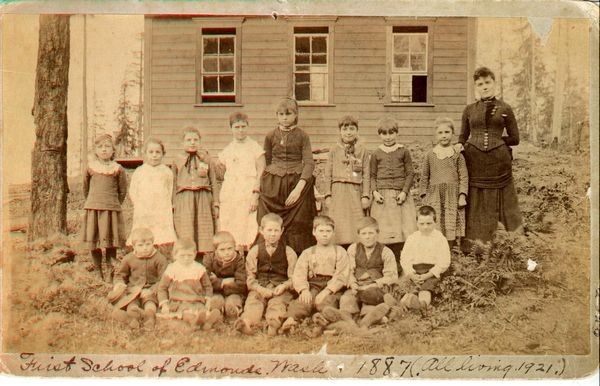 The first school in Edmonds opened in 1884 in George Brackett's feed barn; six students were enrolled.  By 1887 the student population had grown to 15, and the school moved into this one-room schoolhouse located between 3rd & 4th Avenues just north of Main Street.  This 1887 photo shows teacher Miss Taylor and the original 15 students: Maybell White, Fannie Brackett, Ethel Smith, Zetta Fourtner, Flora Deiner, Ruth Hyner , Annie Deiner, Nellie Brackett, Oscar Deiner, Ralph McAlpine, Harry Deiner, George Brackett Jr., Frank E. Deiner, Fred Fourtner, Allen Smith.