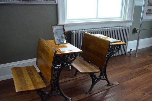 The exhibit contains many classroom artifacts such as these old schoolroom desks with the attached benches.
