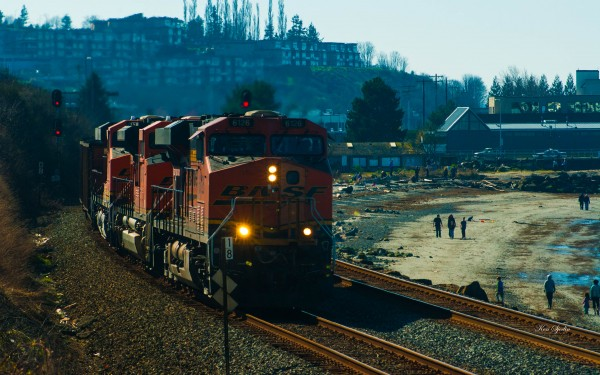 Beachgoers explore during low tide as a BNSF train passes by the Edmonds waterfront earlier this year. (Photo by Ken Sjodin)