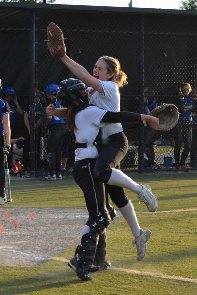 EWHS relief pitcher Mariah Woolery and catcher Jackie Lovelace celebrate the strikeout that ended the game, giving the Warriors a state softball berth. (Photos by Karl Swenson)