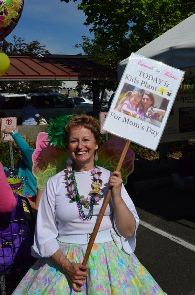 Edmonds in Bloom volunteer Kitt Atkinson gets in the spirit with fairy wings and a hoop skirt.  Atkinson was one of several volunteer who helped the kids choose the right container, the right stickers to decorate it, and the perfect plants. (Photos by Larry Vogel)