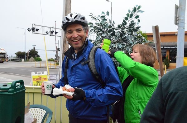 """EBAG's Janice Corbett puts a water bottle in Greg Ransom's backpack.  Greg lives in Richmond Beach and commutes to his job in Mukilteo, which takes him """"a little more than an hour each way."""""""