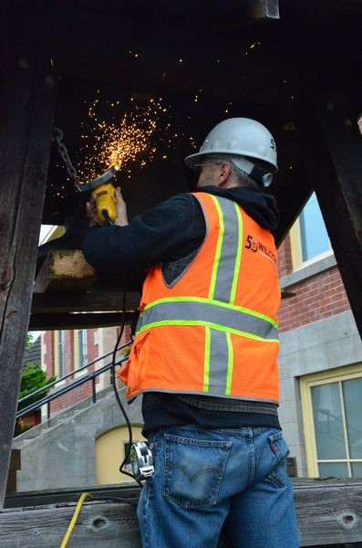 Sparks fly as the metal chains holding the bell to the old structure are cut.