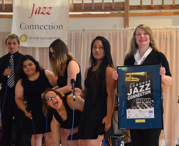 Patti Schmidt, Meadowdale's Avant Blues vocal jazz group director, displays her 2015 Jazz Connection poster while vocalist Peyton Redwood photobombs.