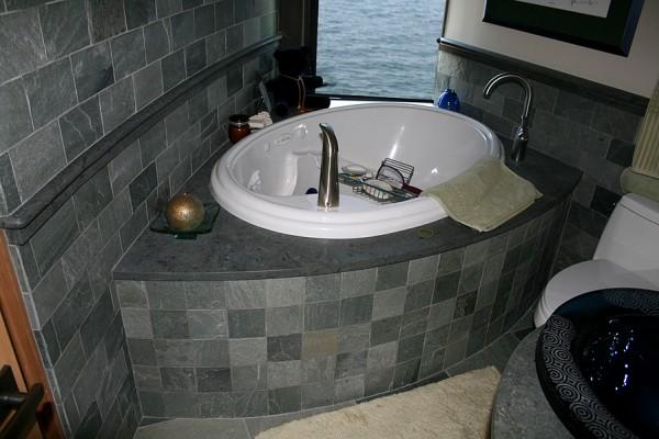 China Green slate bathroom (curved walls) with Burlington slate 1 1/2-inch slab chair-rail cap and tub deck.