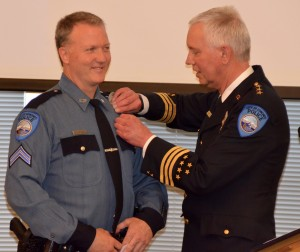 Edmonds Police Chief Al Compaan pins a badge on new Corporal Mark Froland.