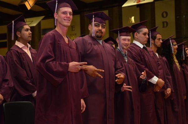 Joshua Abarta, Gerardo Atreaga and Joshua Blair flash the victory sign as they prepare to receive their diplomas.