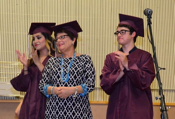 """Retiring principal Cathy Clift, flanked by class speakers Leslie Sanabria and Mitch Fratini, was presented with her own mortarboard in honor of her """"graduation"""" into retirement after a 40-year career in education, the last 13 of which were spent a principal of Scriber Lake High School. (Photos by Larry Vogel)"""