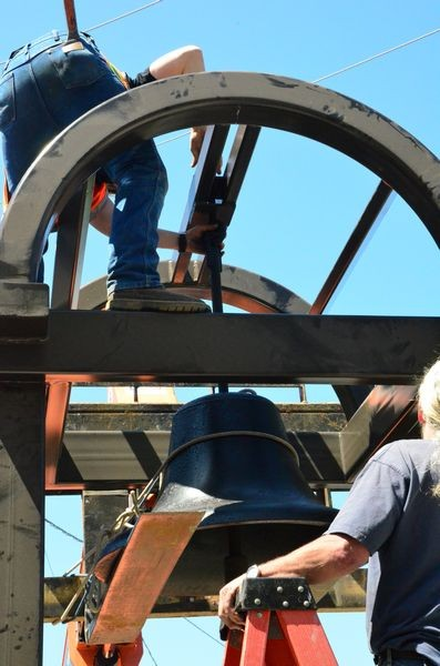 Crews attach the bell to the new tower.