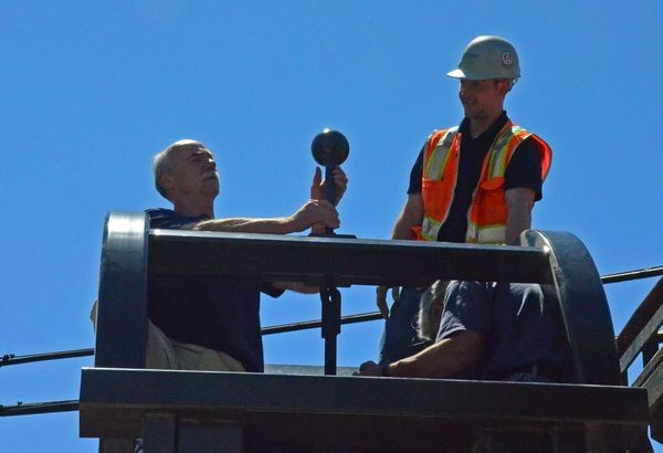 Plaza designer Clayton Moss places the filial on the top of the new bell tower.