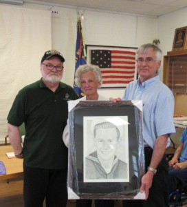 Mike Reagan, left, presents the portrait to Helen Gaasland and her son Greg.
