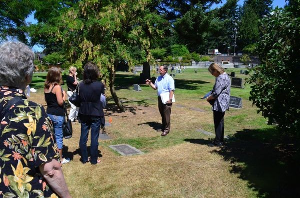 The Edmonds Cemetery Board held its annual Walk Back in Time event Thursday at the Edmonds Memorial Cemetery.  Each year on the third Thursday in July the Board conducts a tour of the grave sites of significant figures from Edmonds history. This year's tour highlighted past mayors of Edmonds. Here current Cemetery Board chair Jerry Janacek tells the story of Mayor Fred Fourtner, who held the office from 1927-1933, and again from 1937-1949, making him the longest-serving mayor in the history of Edmonds. (Photo by Larry Vogel)