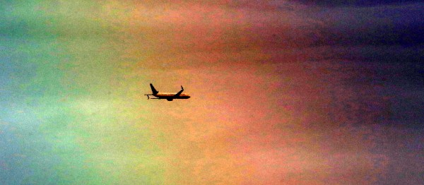 """I was photographing birds at the marsh Saturday evening with my large telephoto lens. A brief shower produced a rainbow in the eastern sky as an airplane heading towards SeaTac flew past. The rainbow did not show up well in my original photos.  I used a post processing feature called """"autocontrast"""", which turned the photos  into a psychedelic flight of fancy."""