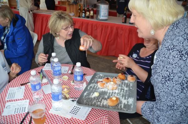 Tasteoff coordinator Theresa Poalucci right, serves Hawaiian doughnuts -- another judges' favorite -- to Cheryl Reagan.