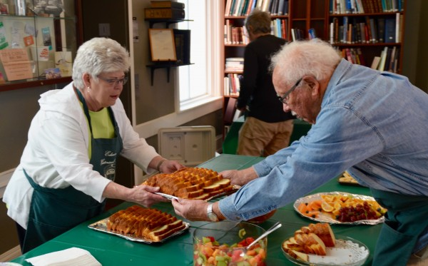 Margaret and Mike Wilcox, museum volunteers who have been working with market vendors for 18 years, replenish the food supply.