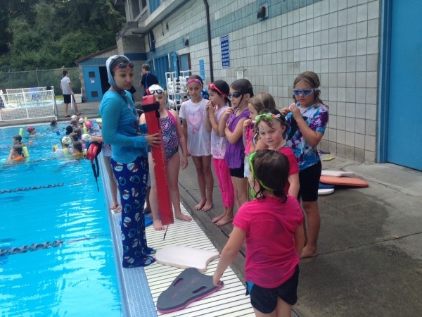 """Yost Swim Team's 2015 season is wrapping up. Earlier in the week, swimmers had a blast practicing in """"Drag,"""" or fully dressed. The purpose was twofold: to practice swimming with resistance, but also to familiarize youth with the feeling of being in the water fully clothed. Coach Gilliam Lim presented younger students a class on rescue techniques, and how to safely aid a distressed swimmer. Yost Penguins will participate in the Championship meet at Snohomish Aquatics Center all day Saturday. We wish them luck!"""